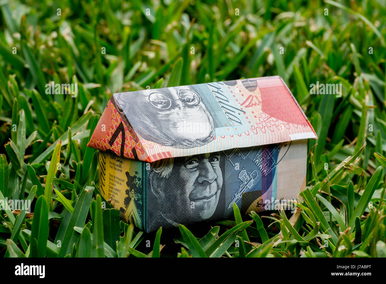 Origami house made with Australian Notes sitting on grass Stock Photo