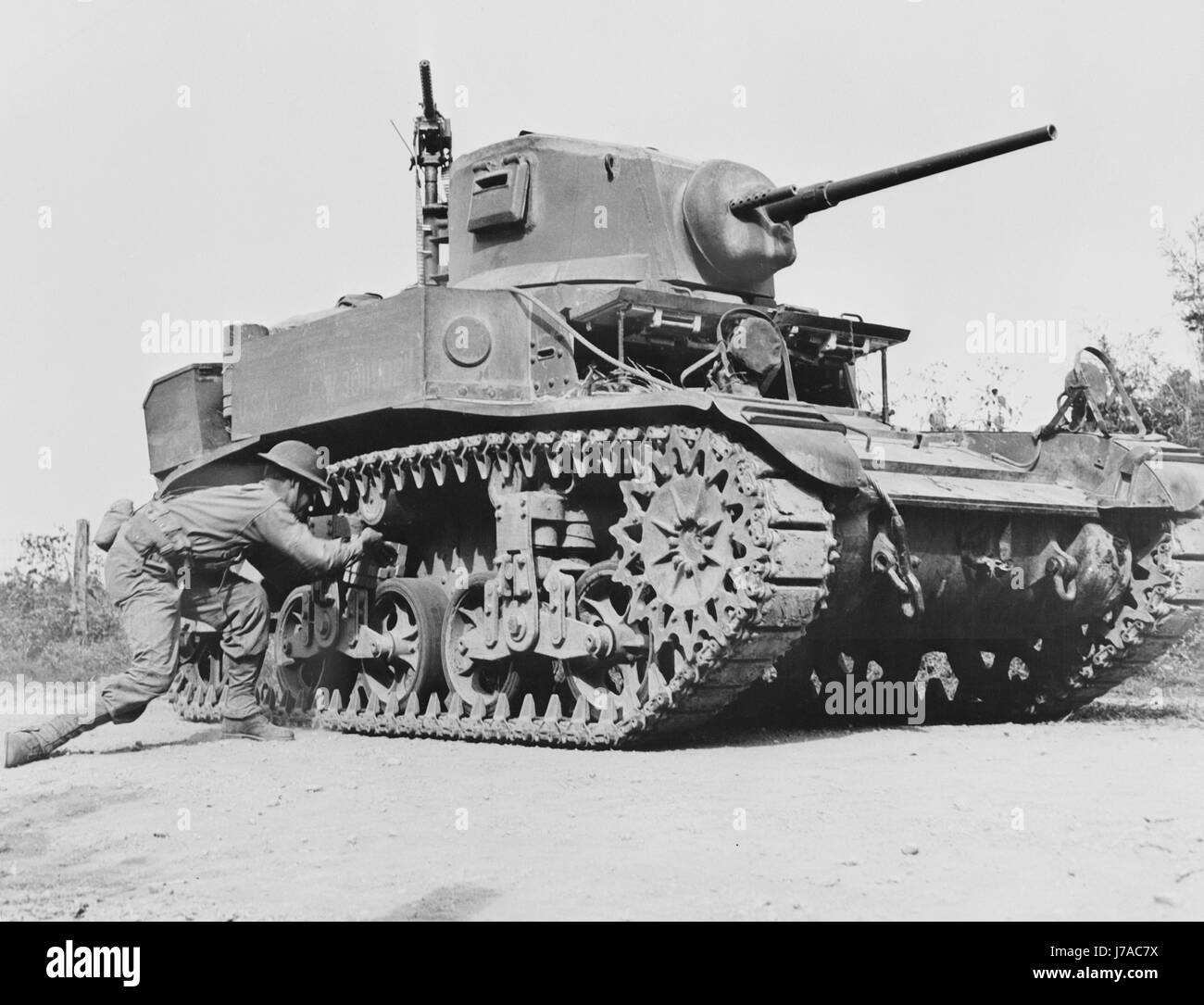 A soldier places a 29 pound TNT statchel charge on a light tank, circa 1942. - Stock Image