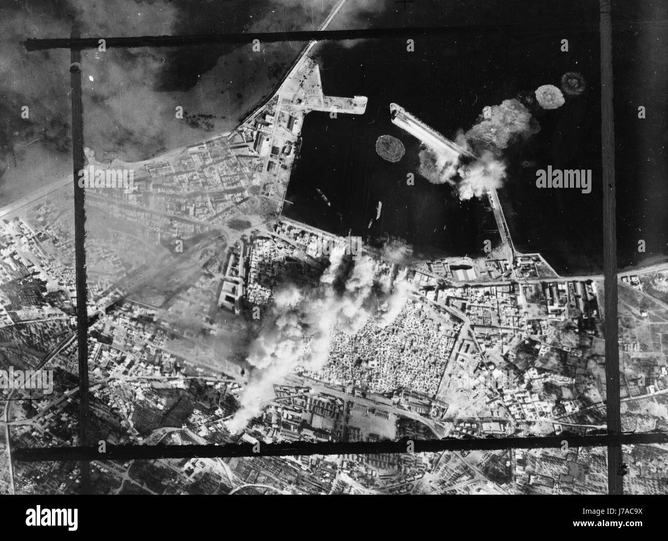 Aerial photograph showing direct bombing hits on a pierhead in Sousse, Tunisia, circa 1943. - Stock Image