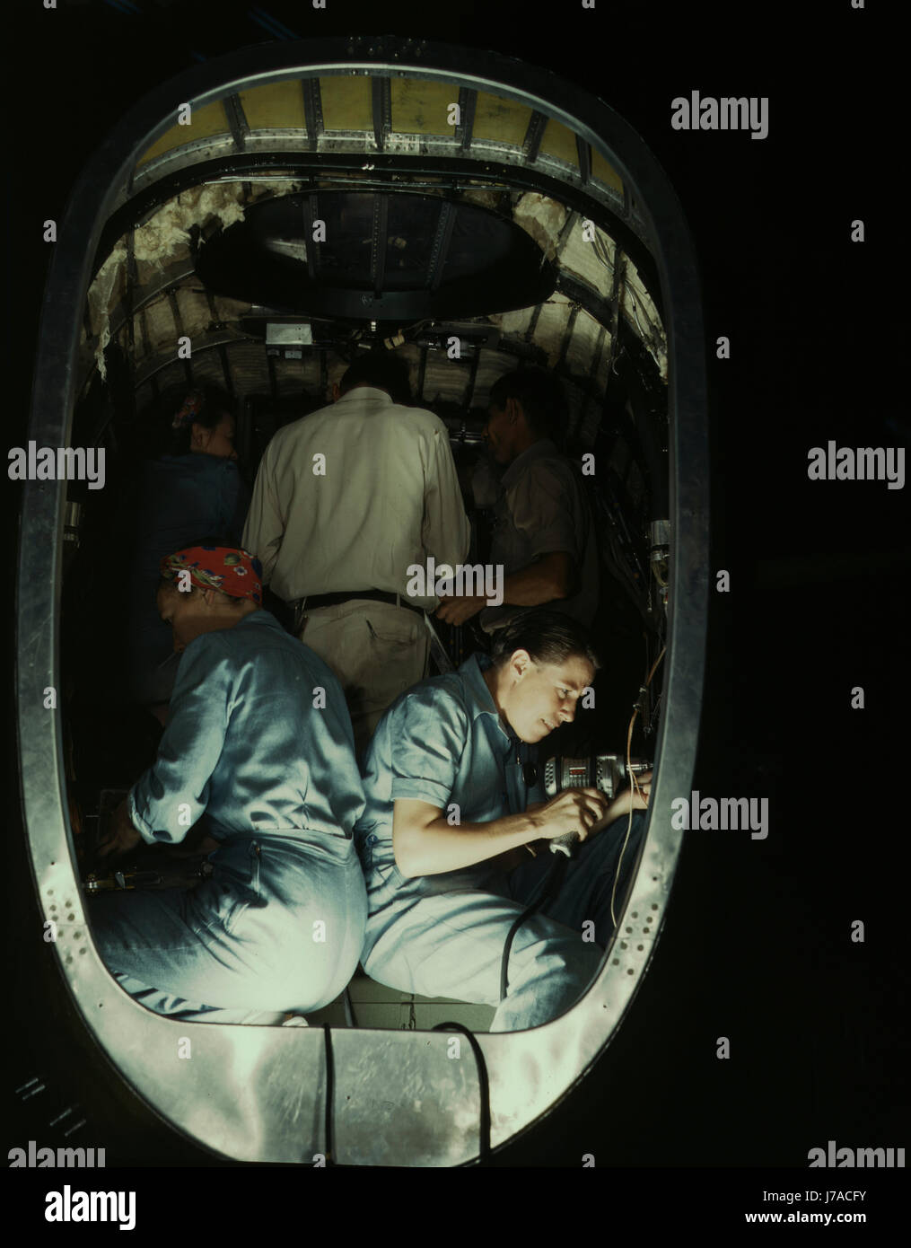 People working inside fuselage of a Liberator Bomber, 1942. - Stock Image