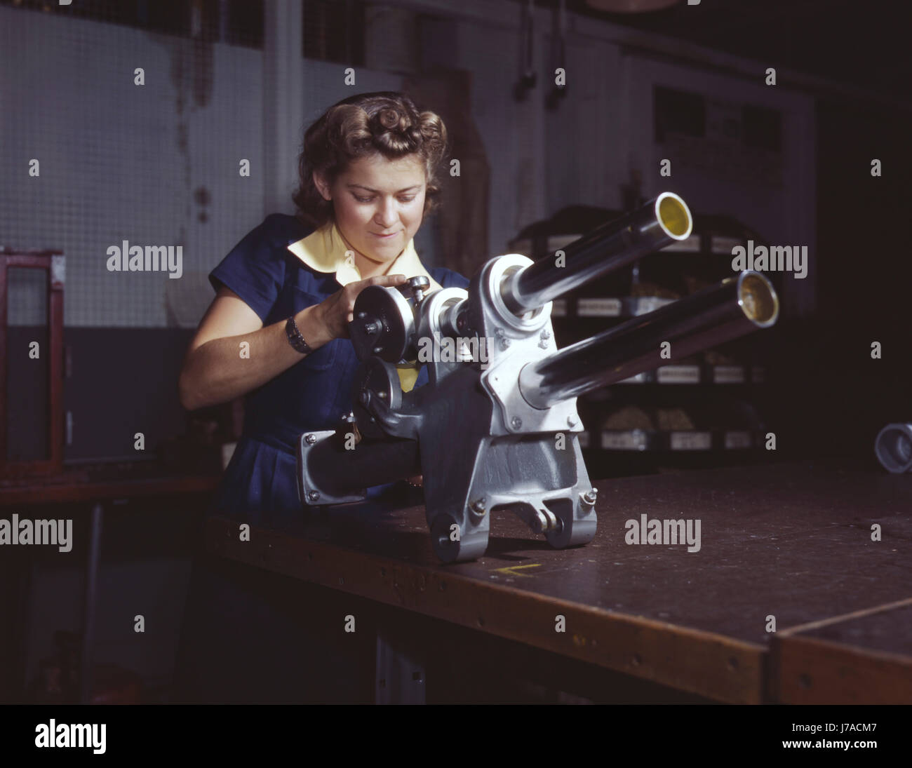 A young woman working over the landing gear mechanism of a P-51 fighter plane, 1942. - Stock Image