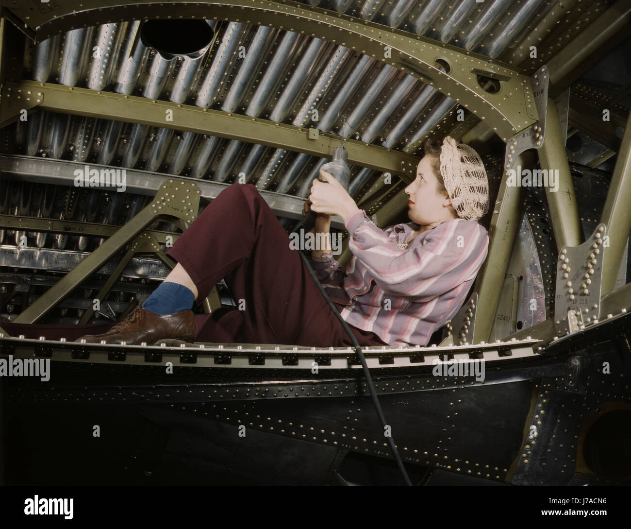 An A-20 bomber being riveted by a woman worker, 1942. - Stock Image