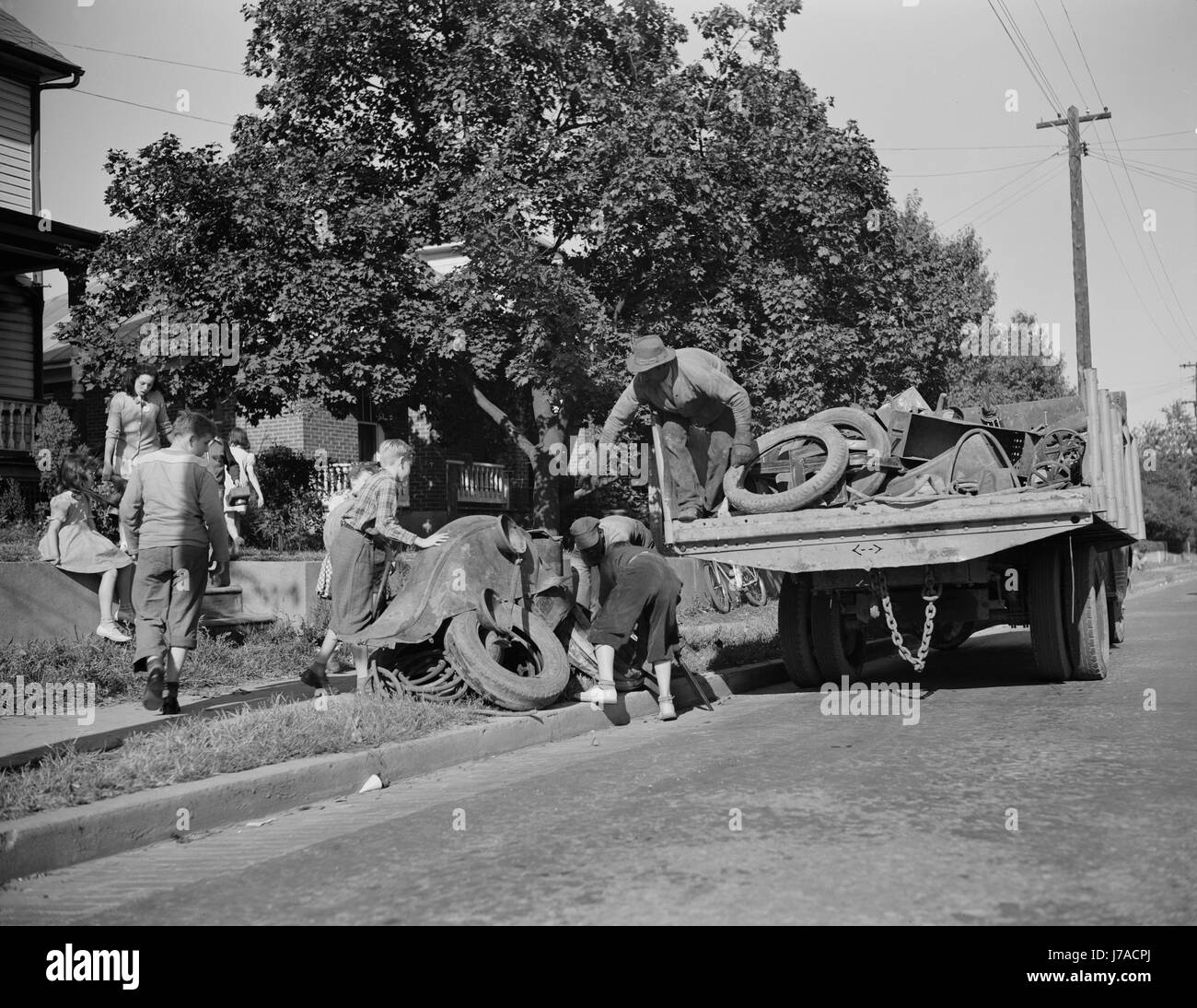 Youngsters help load a truck with scrap metal for donation to their war industries, 1942. - Stock Image