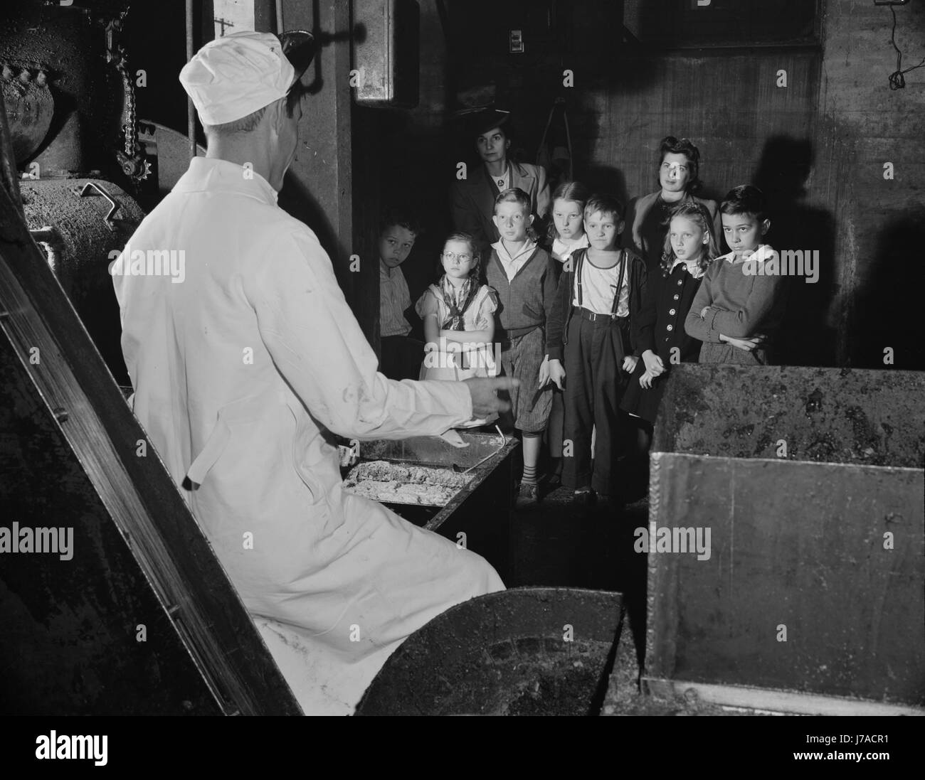 Children visit the local rendering plant to learn how explosives are made from fats and grease, 1942. - Stock Image