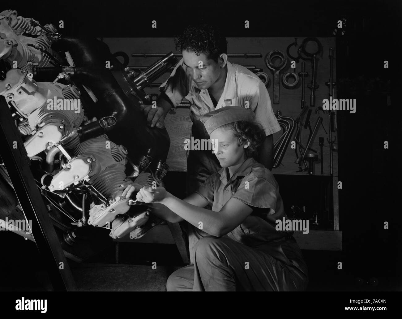 An expert mechanic shows a student the tricks of an airplane motor, 1942. - Stock Image