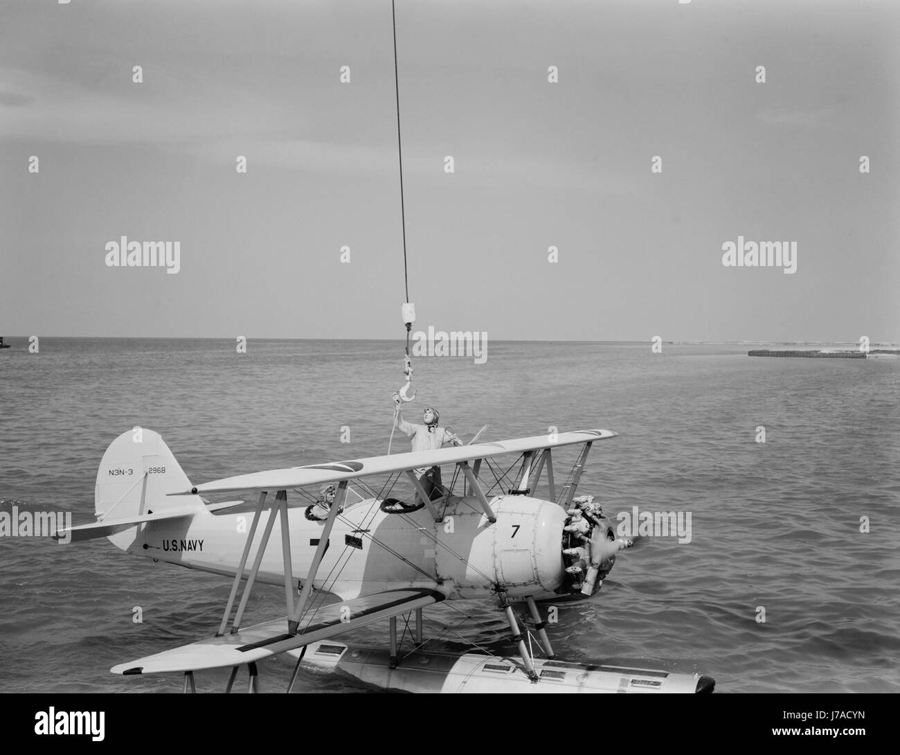 A U.S. Navy N3N seaplane being attached to a hook, then hoisted out of the water, 1942. - Stock Image