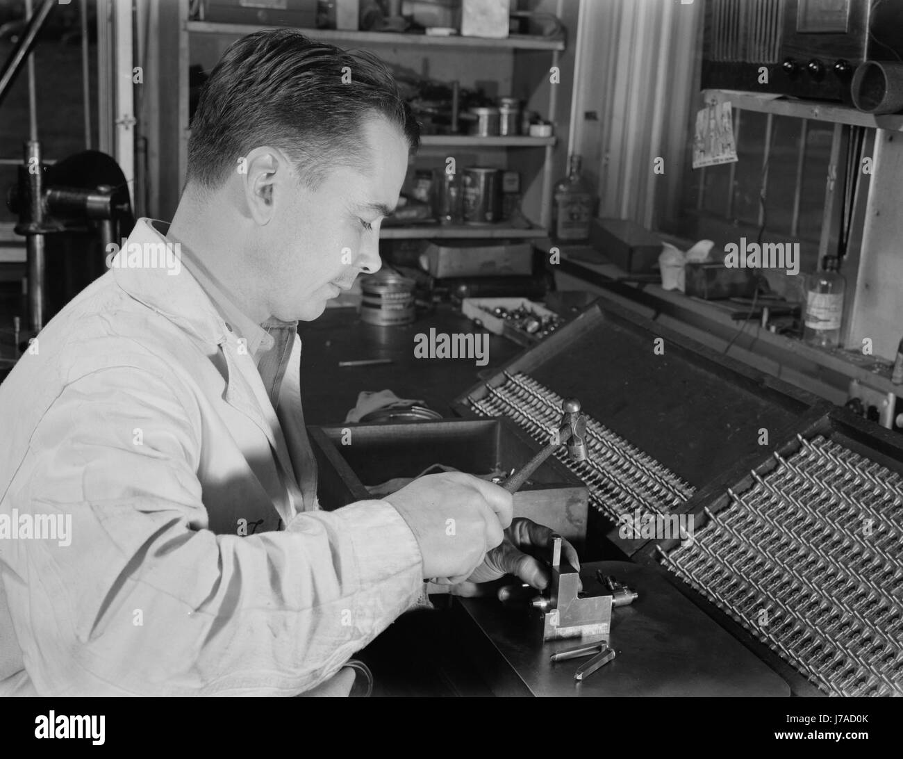 A local subcontractor numbers the barrels of the valves for blood transfusion bottles. - Stock Image