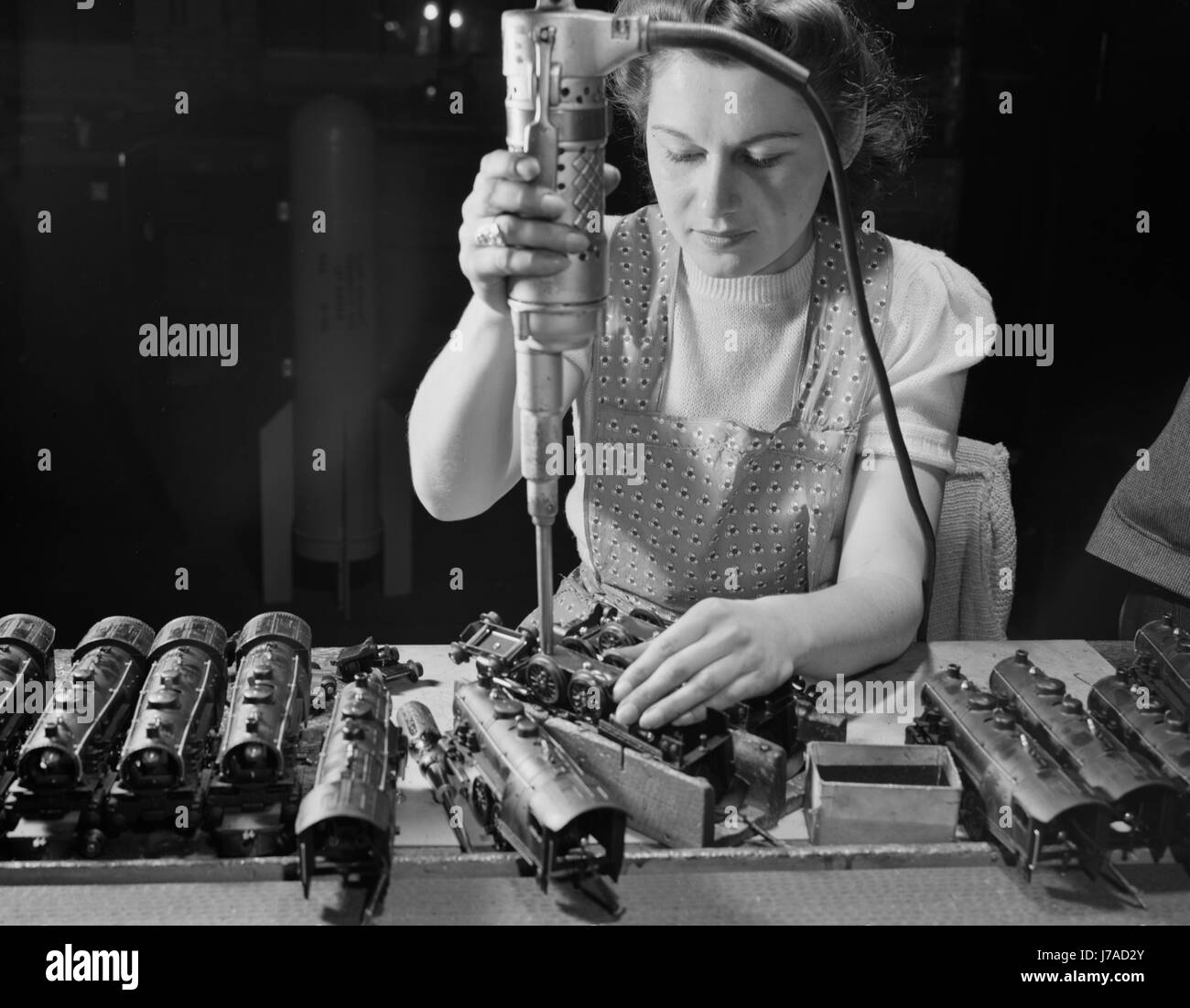 Woman worker using an electric screwdriver to assemble toy trains, 1942. Stock Photo