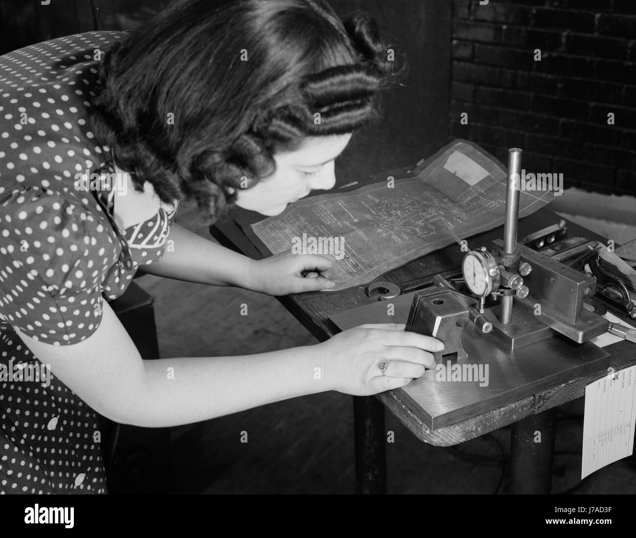 Woman factory worker checks completed V-blocks with blueprint specification, 1942. - Stock Image