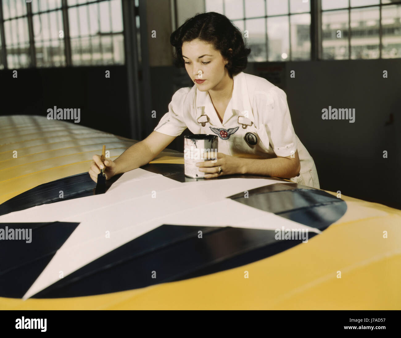 A female worker paints the American insignia on a Navy plane wing, 1942. - Stock Image