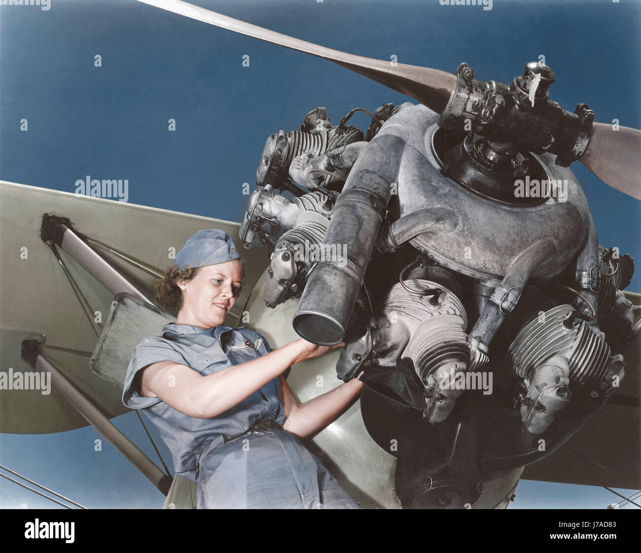 A 20 year old woman and expert aviation mechanic rebuilding an airplane engine. - Stock Image
