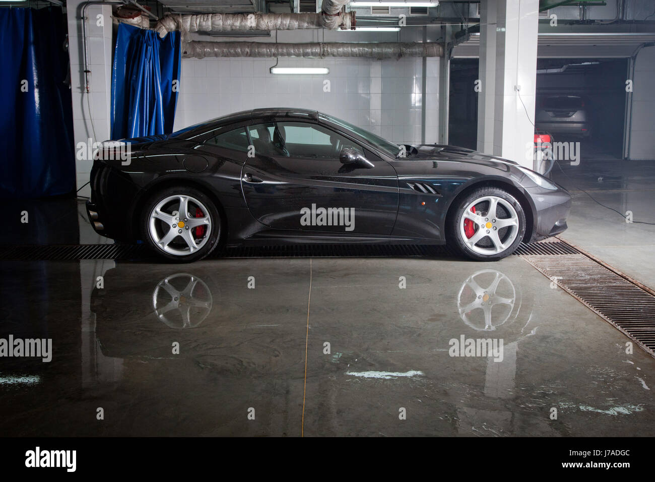 Black sportcar in car wash - Stock Image
