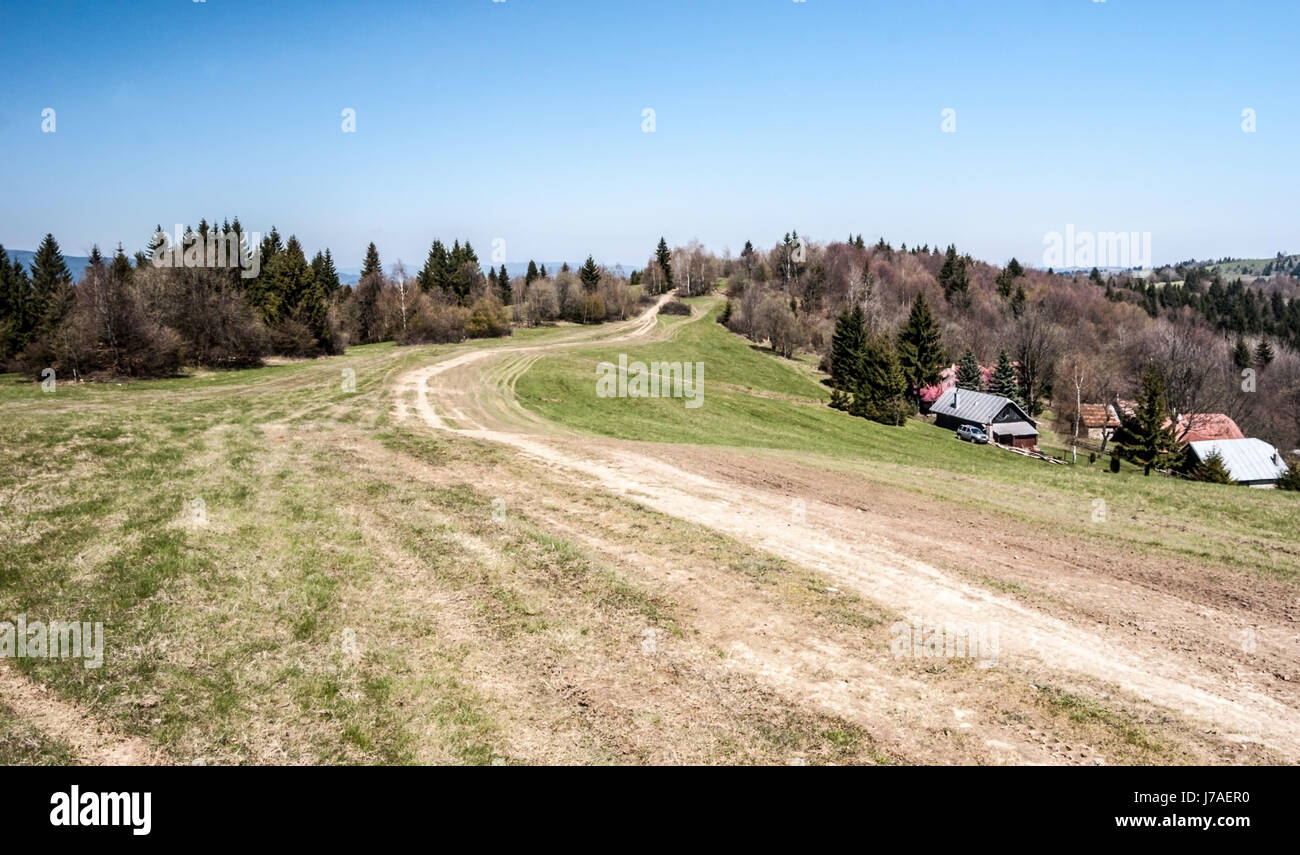 mountain meadow with hiking trail, few houses, forest and clear sky bellow Jakubovsky vrch in Javorniky mountains Stock Photo