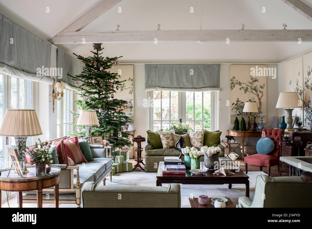 Spacious and light filled living room with old Chinese painted panels and large chirstmas tree. The pastel hued - Stock Image