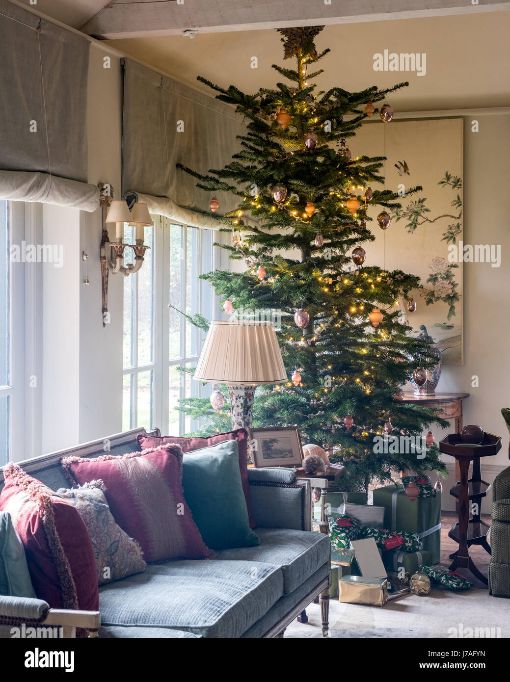 Tall christmas tree in corner of spacious sitting room with settee and old chinese painted panels. The sofa upholstery - Stock Image