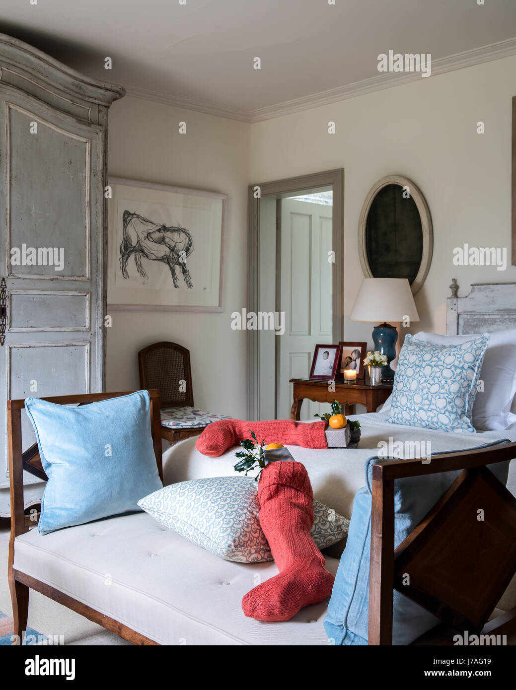 Christmas stocking on antique banquette in elegant bedroom. The charcoal drawing of a cow is by artist Jason Gathorne - Stock Image