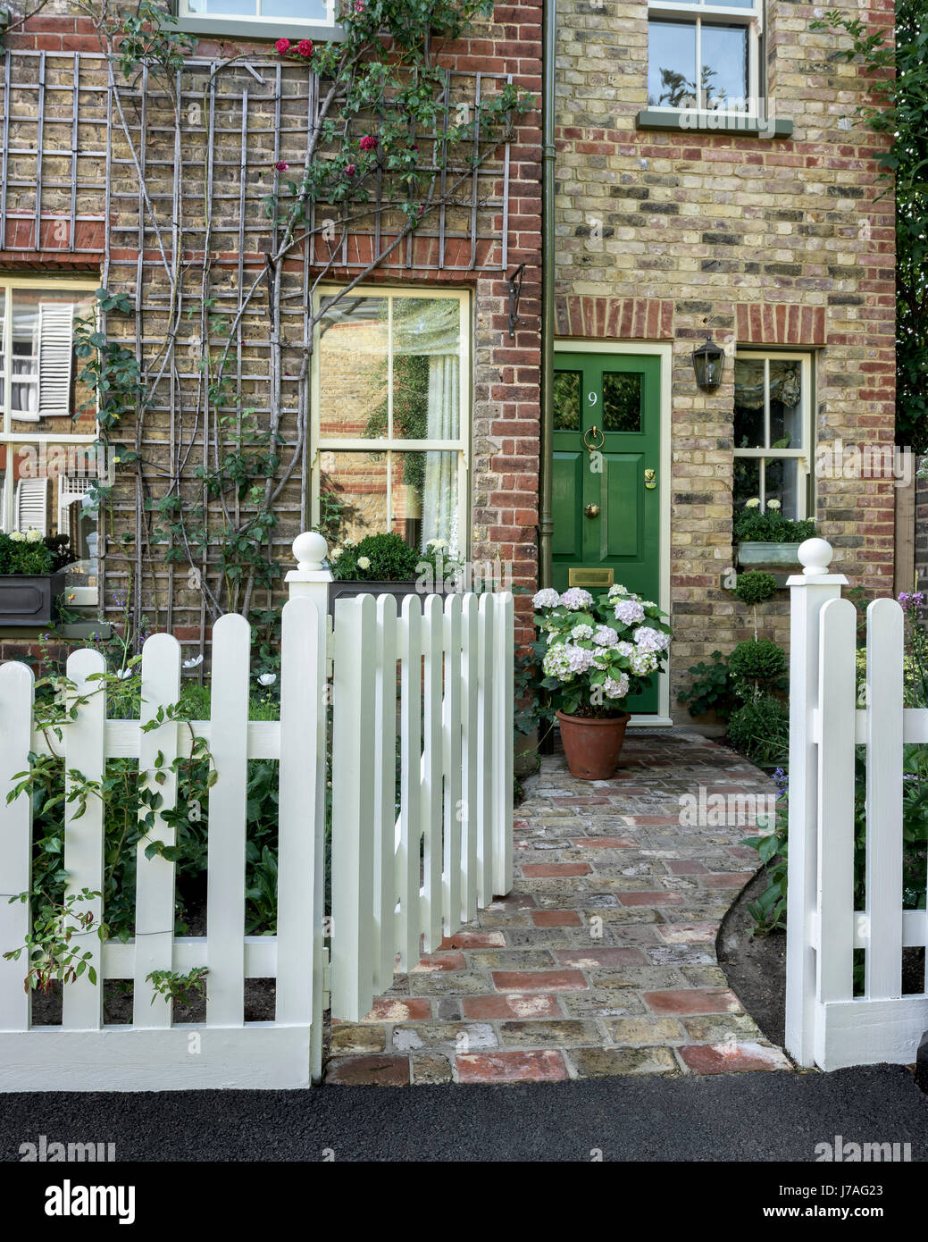 Exterior Facade Of Late Victorian Cottage With Tiled Path And Green Front  Door