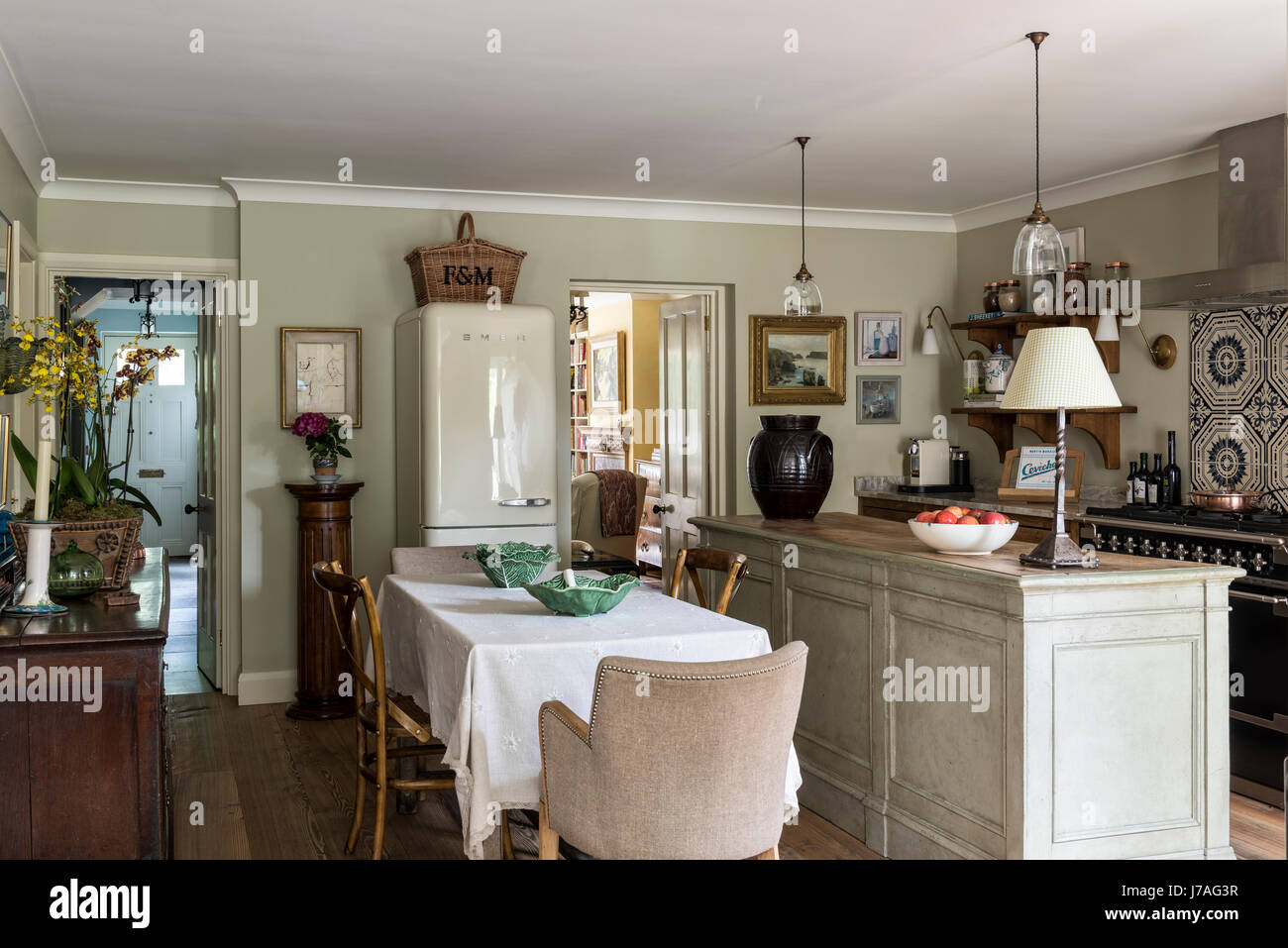 Elegant traditional feeling kitchen with antique dining table and chairs, Smeg fridge and butchers island. The pendant - Stock Image