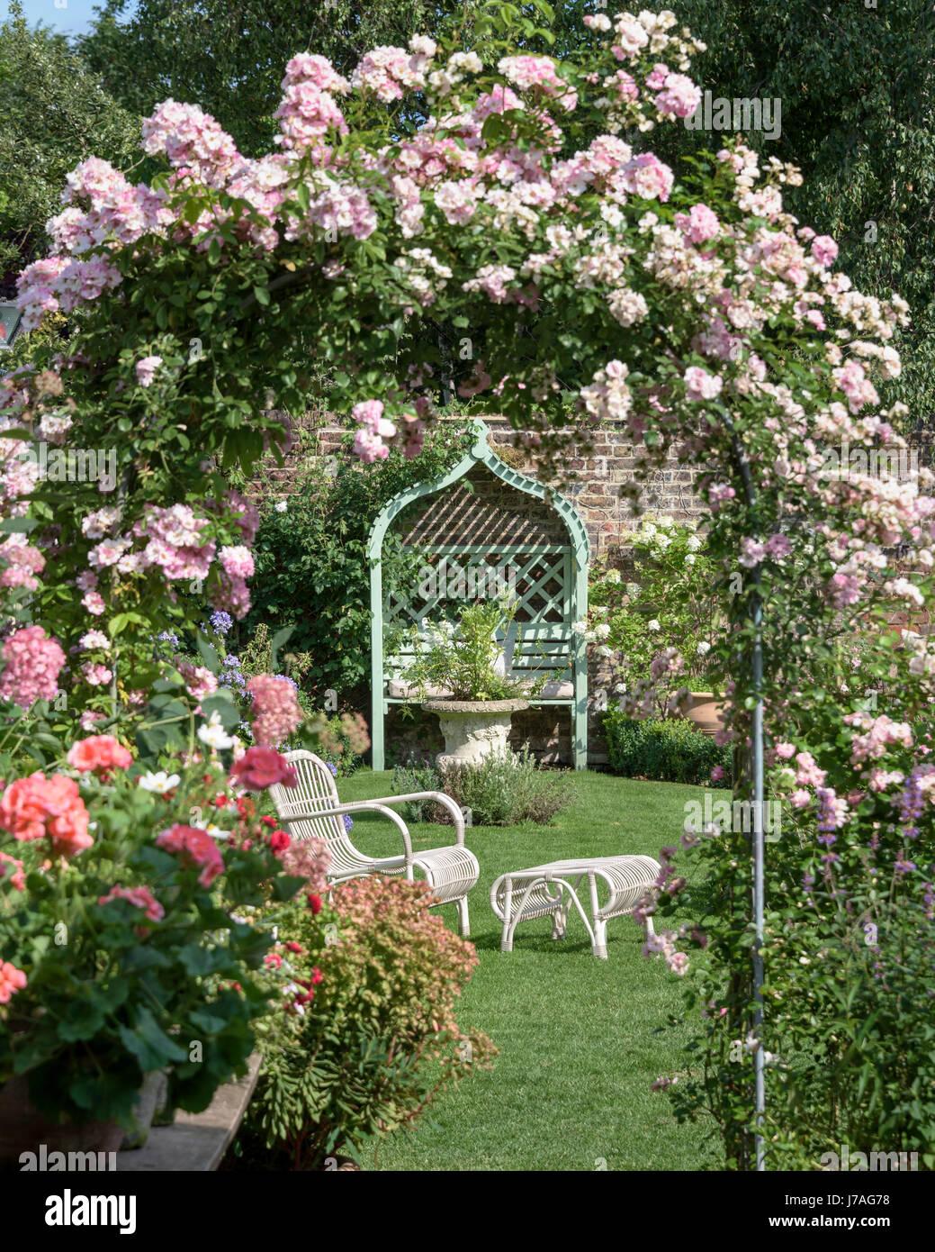 Wicker Garden Furniture Seen Through A Rose Arch In An English