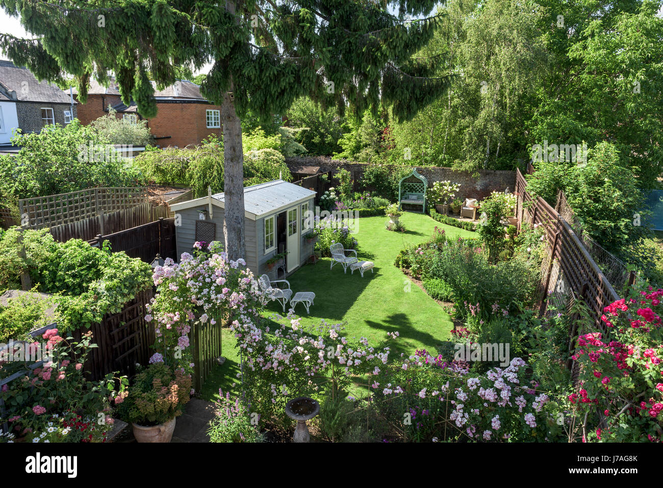 View from balcony down to english walled garden with summer house and rose arch - Stock Image