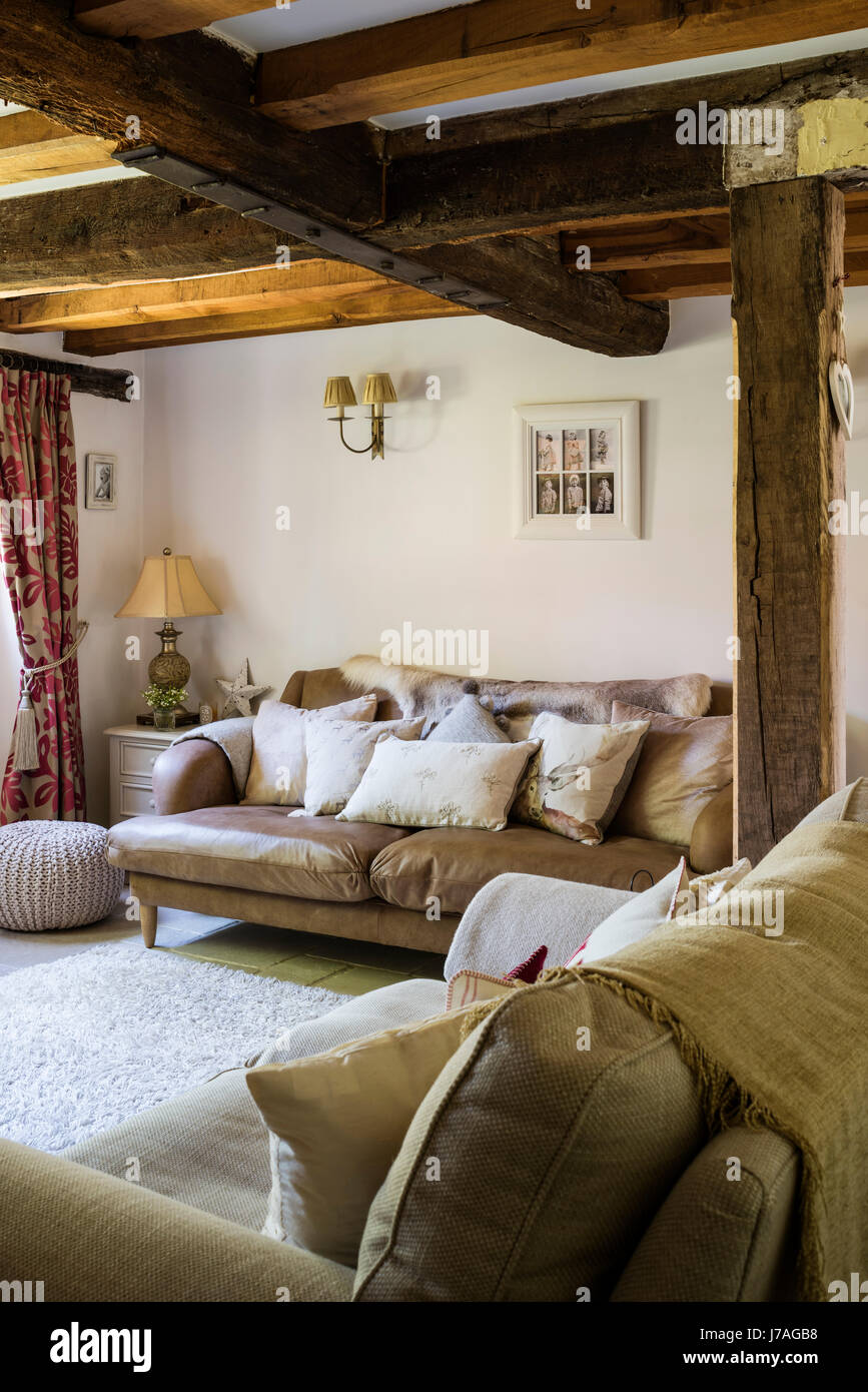 Cosy sitting room with wood beamed ceiling. The leather sofa is from Loaf and the rug from John Lewis - Stock Image