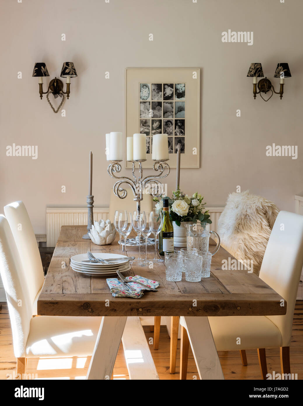 Airy dining room with large wooden table and wooden flooring. The dining chairs are from Next and the fleece is - Stock Image