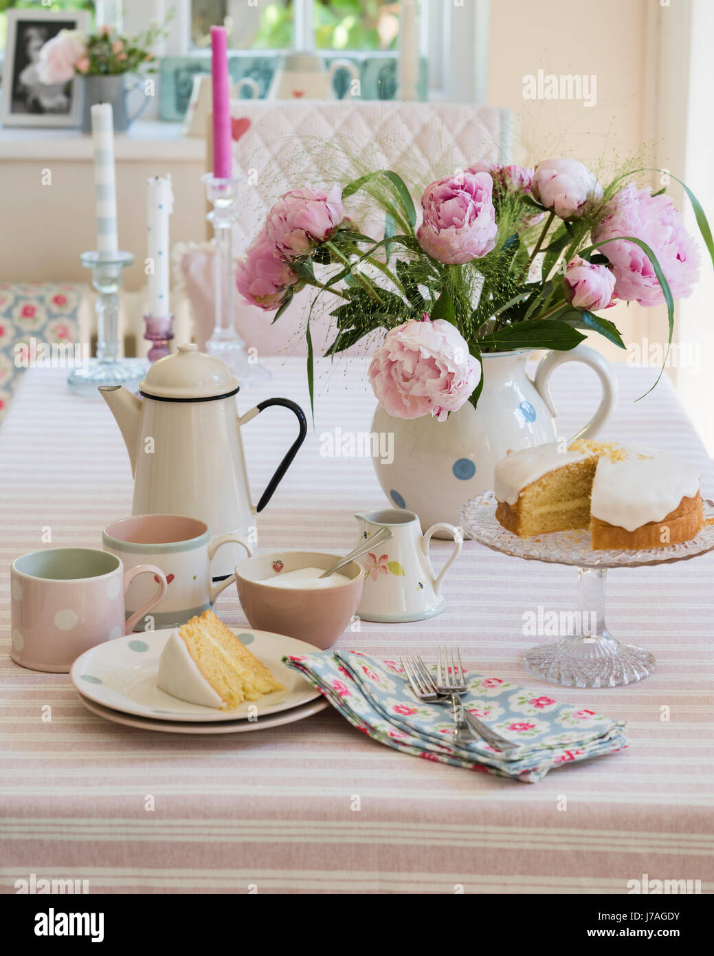 Sponge cake, enamel teapot and pink peonies on striped table cloth from Susie Watson Designs - Stock Image