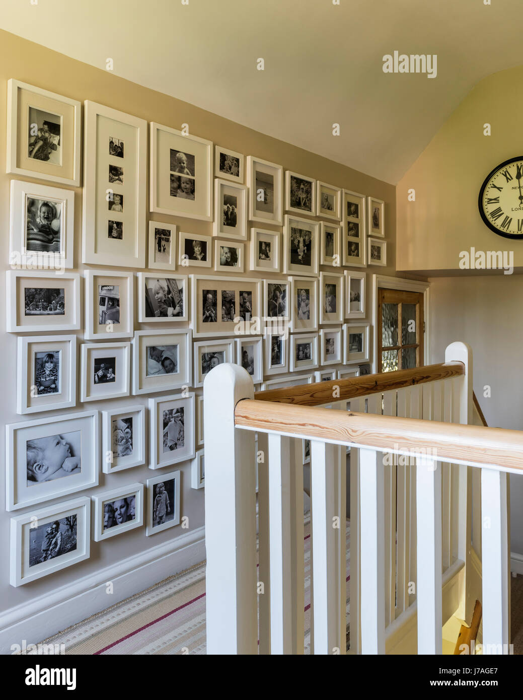 Framed black and white family photography along wall on staircase landing - Stock Image
