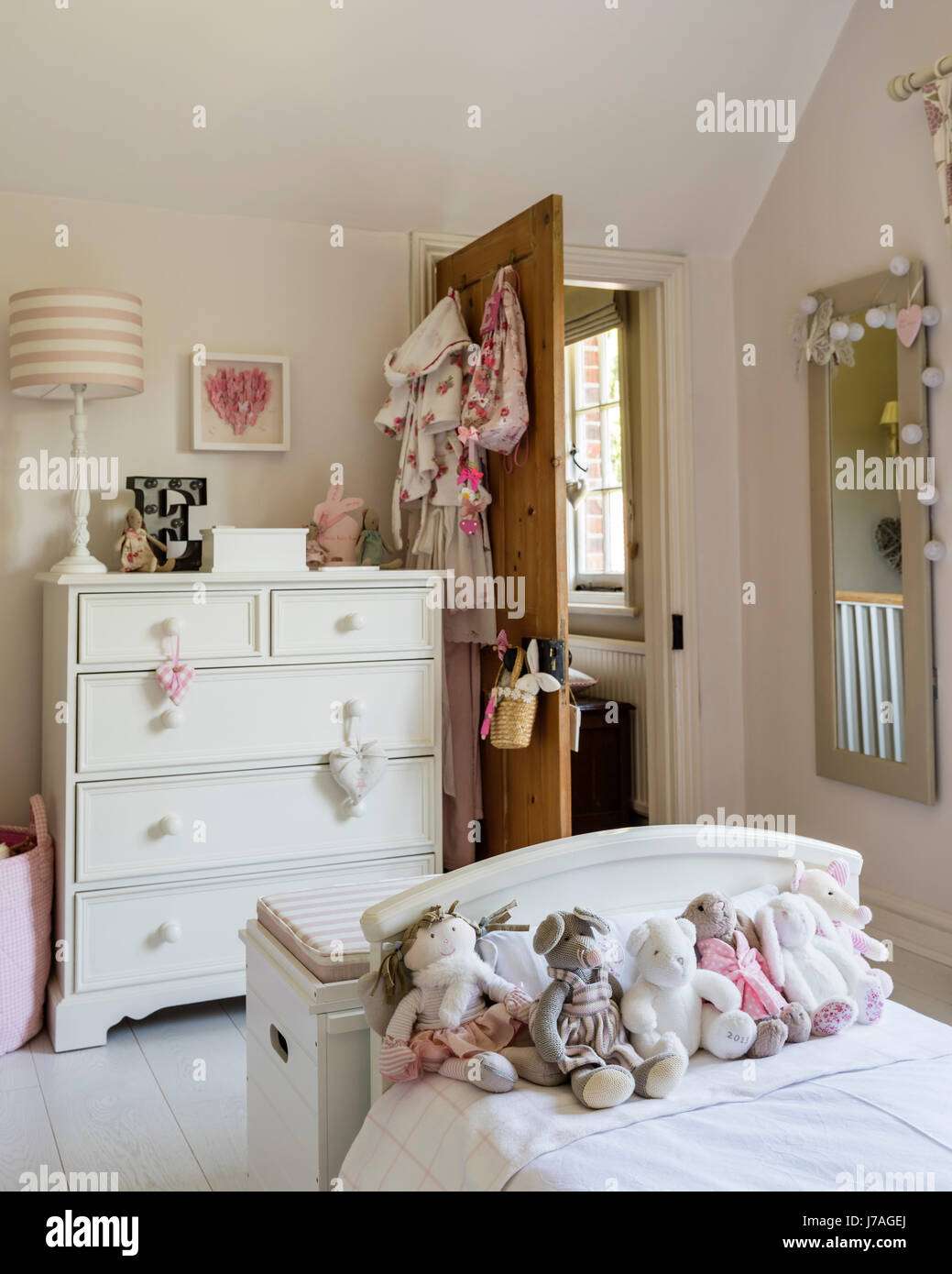 Assorted teddy bears on bed in childs bedroom, the chest of drawers is painted in Farrow & Ball's Pointing by Fairlily Stock Photo