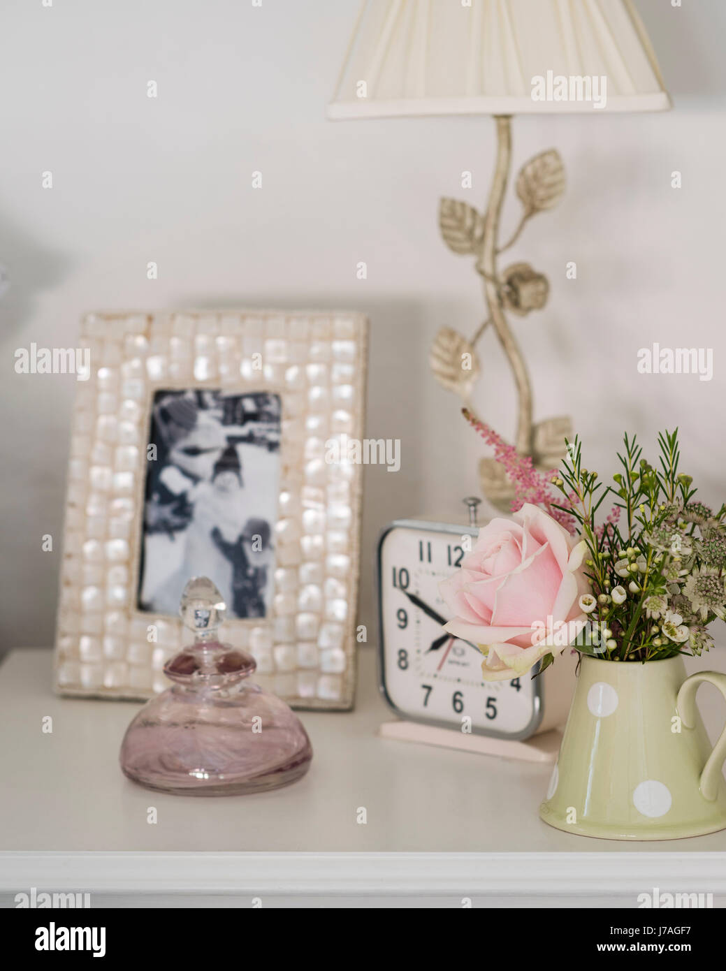 Detail of bedside table with alarm clock, framed photograph and posey of flowers - Stock Image
