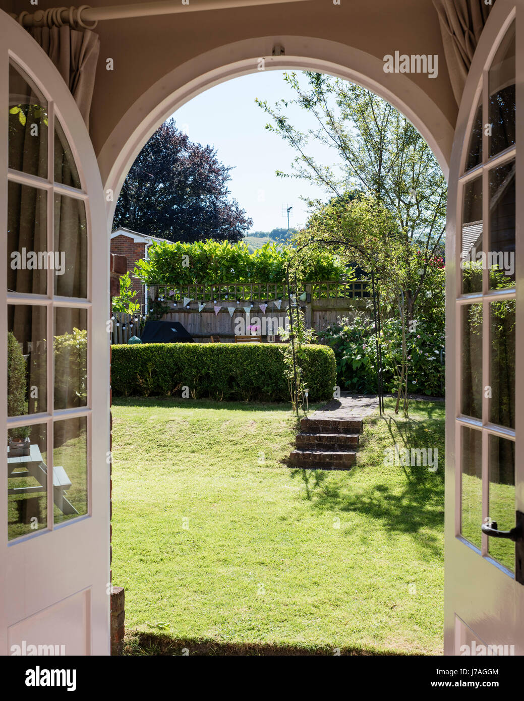View through arched french doors to small country garden - Stock Image