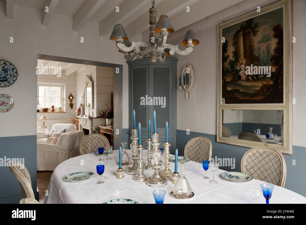 Silverware candlesticks on dining table with corner cabinet and 18th century French trumeau mirror - Stock Image