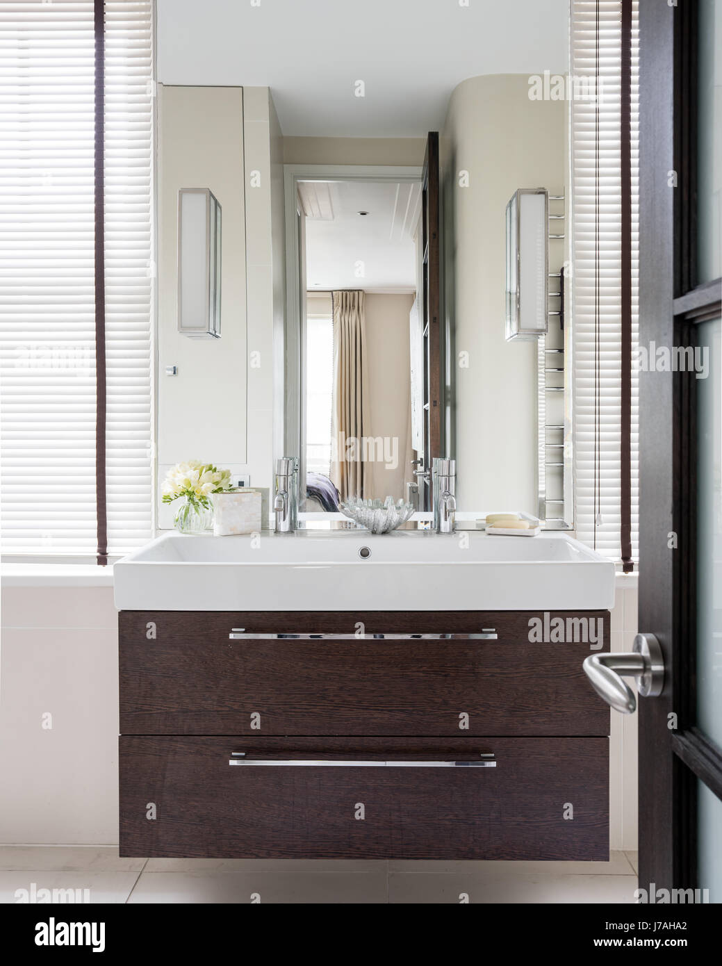 Mirror above rectangular basin in two drawer unit with walnut finish ...