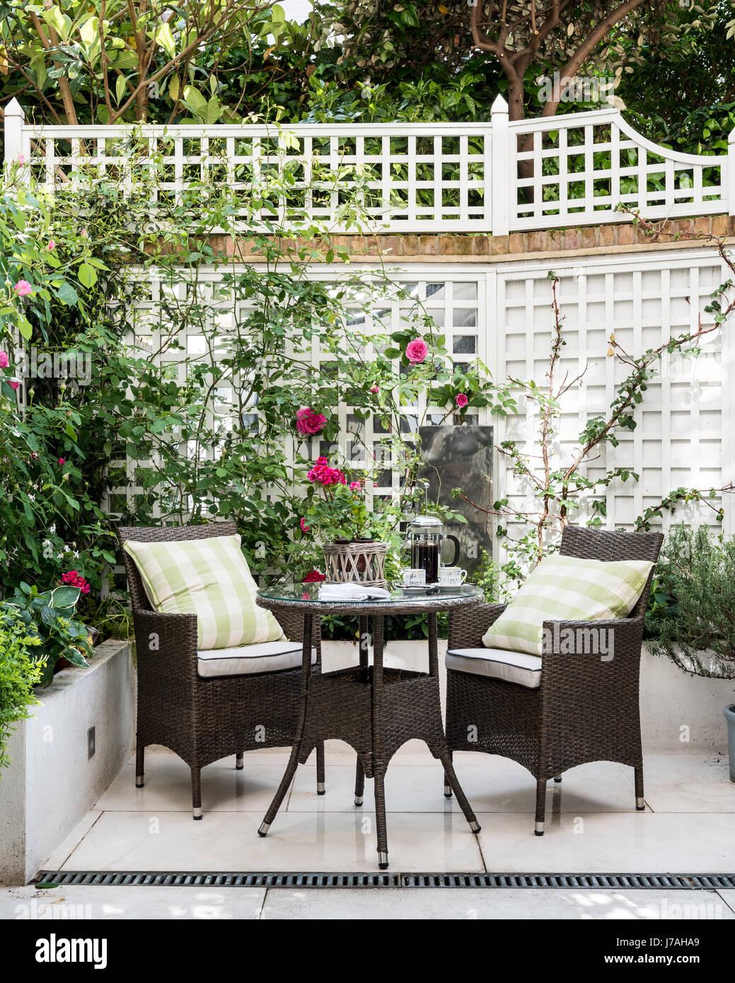 Wicker furniture in courtyard garden of Victorian terrace, London Stock Photo
