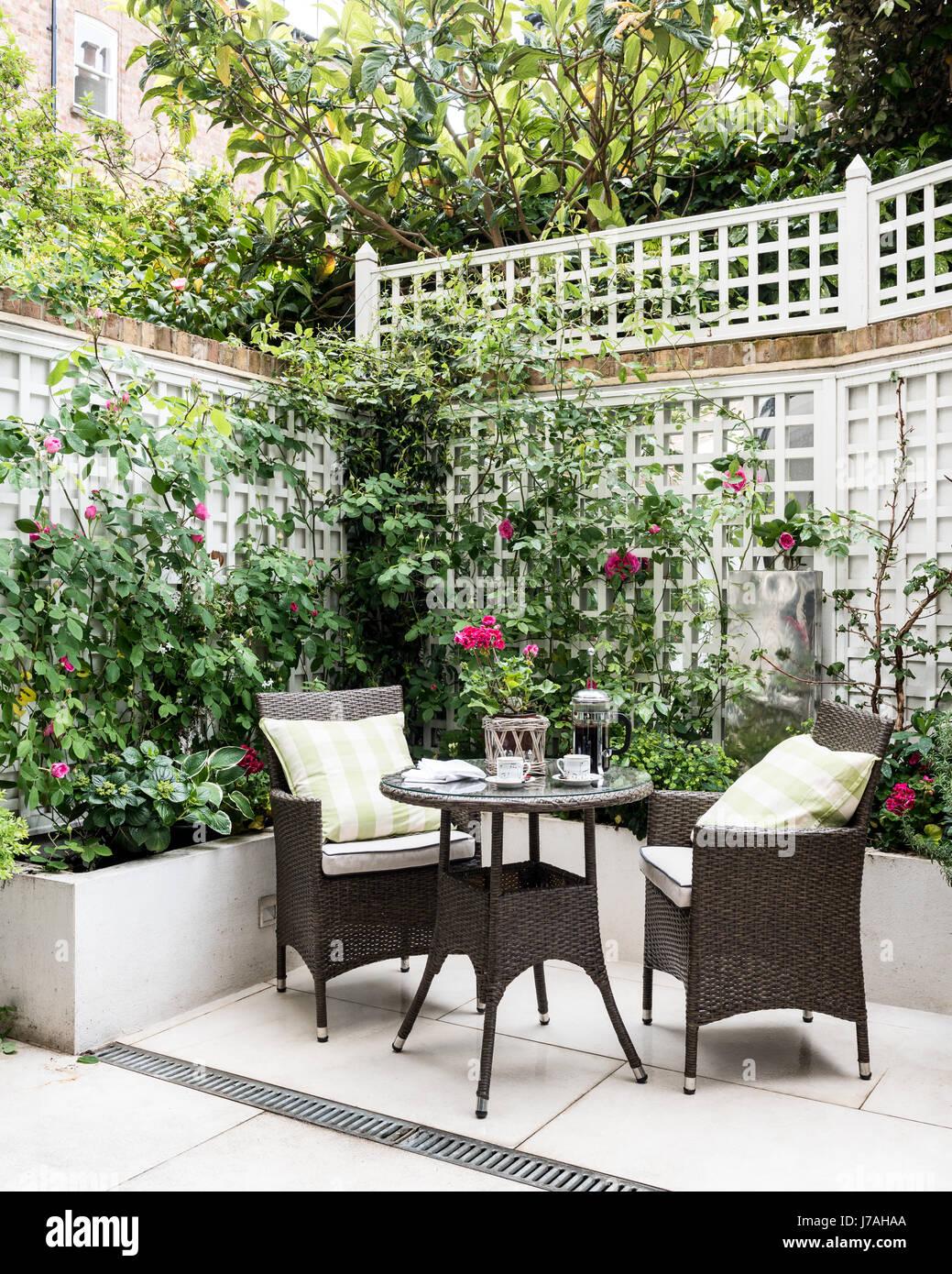 Wicker furniture in courtyard garden of Victorian terrace, London - Stock Image