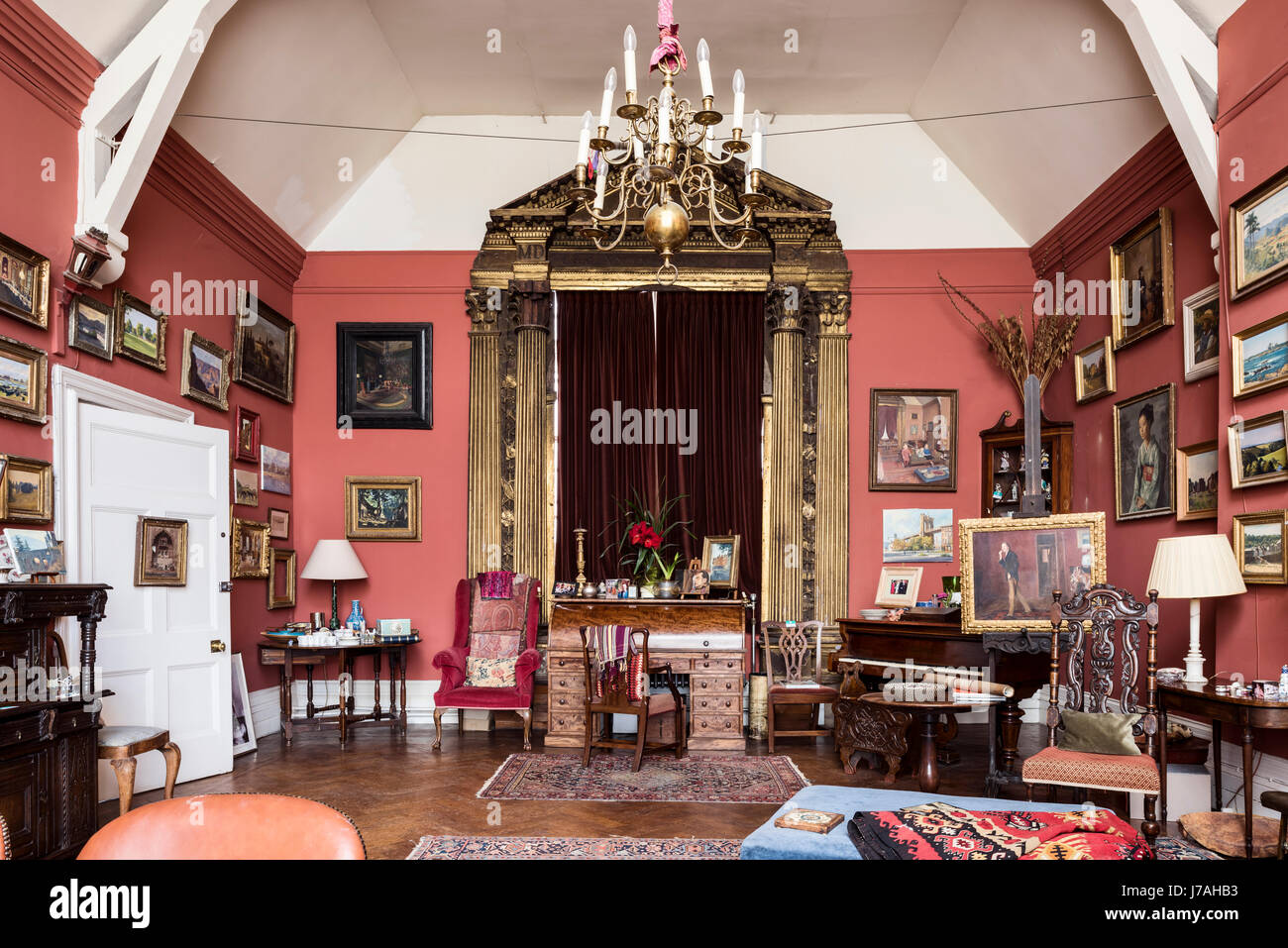 A large salvaged gilt wooden 15th century overdoor and pediment around velvet curtain window in drawing room painted - Stock Image