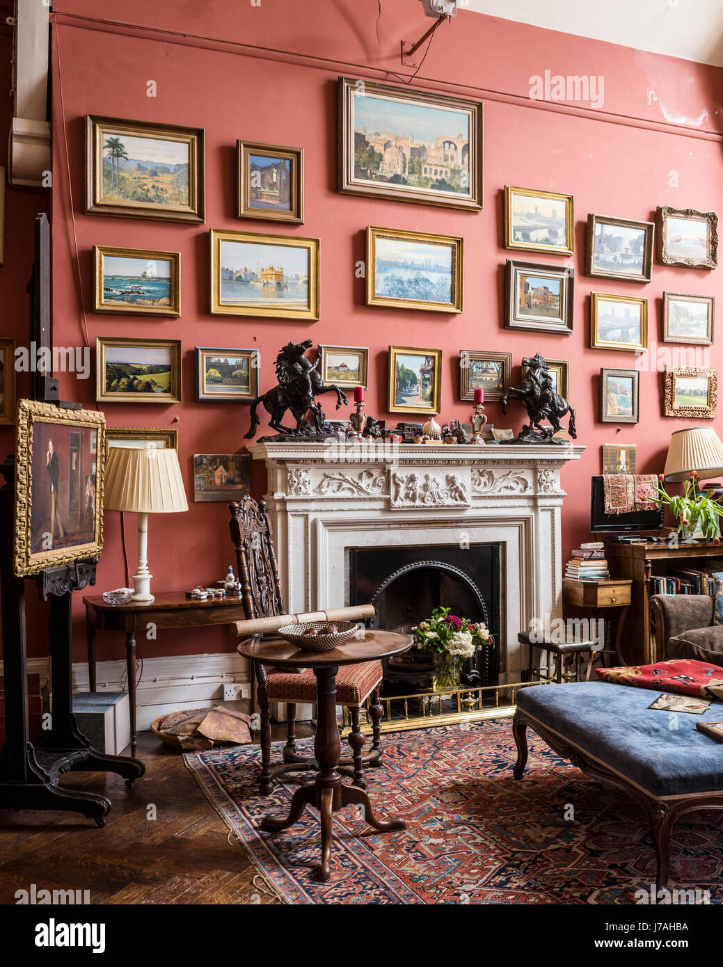 A collection of Julian Barrow paintings above a salvaged chimney piece with blue velvet ottoman. The walls are painted - Stock Image