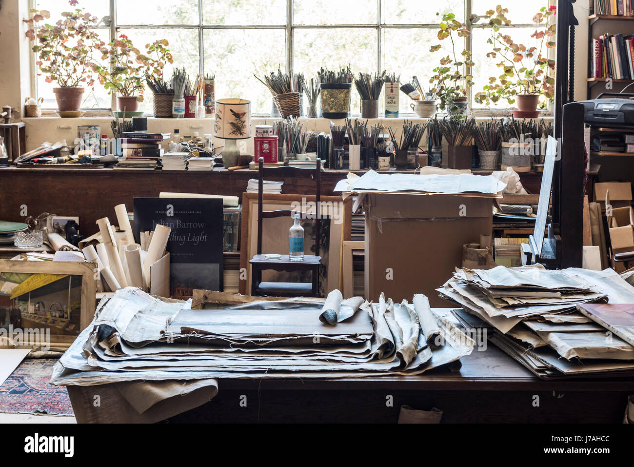 Unframed canvasses and paint brushes in jars in bohemian artists studio with large window - Stock Image