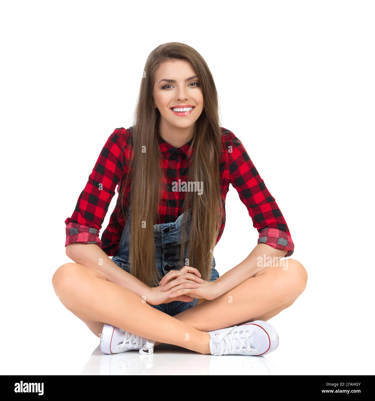 Young smiling woman in red lumberjack shirt, jeans shorts and white sneakers sitting on a floor with legs crossed - Stock Image