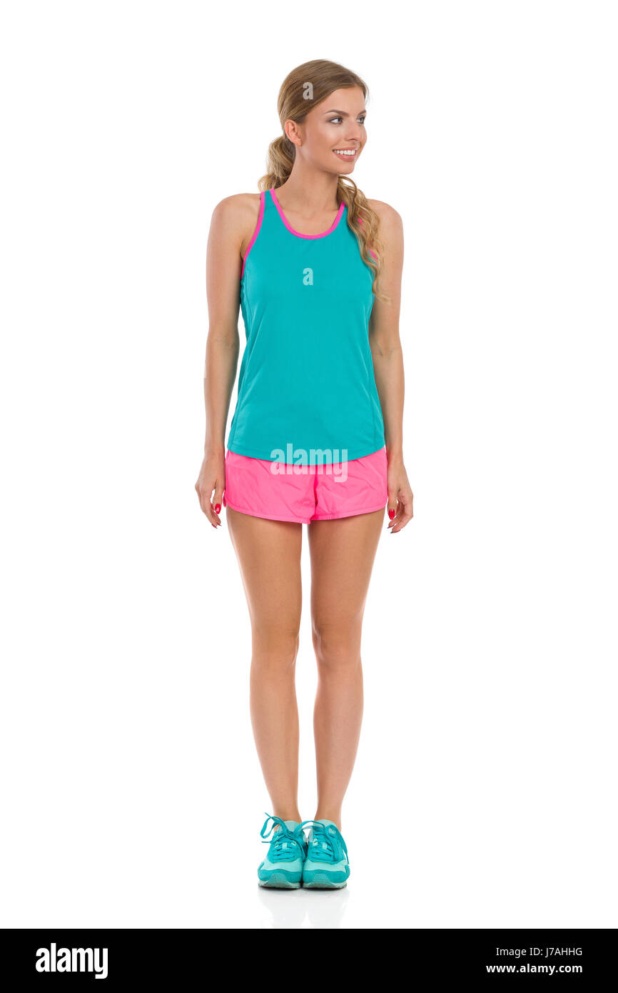 Cheerful beautiful young woman in pink shorts, turquoise tank top and sneakers standing at attention and looking - Stock Image