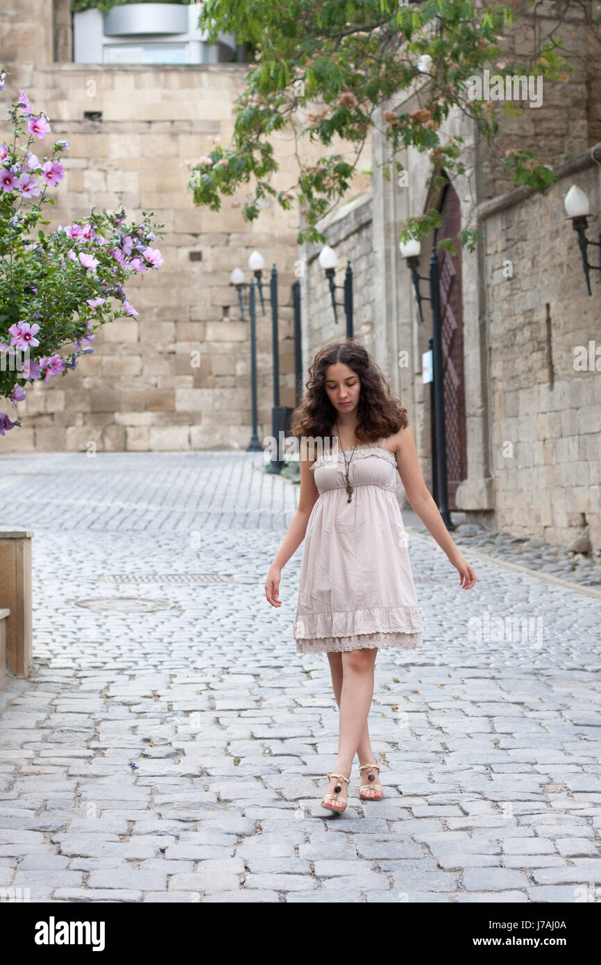Full length portrait of curlie young girl wearing biege romantic dress strolling through old streets of Inner City - Stock Image