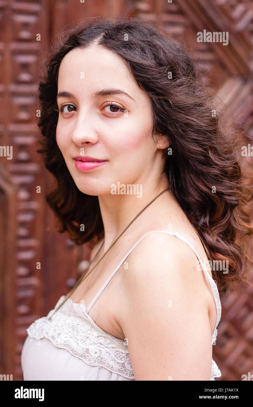 Close up portrait of young curly brunette in front of brown vintage door made of carved wood - Stock Image
