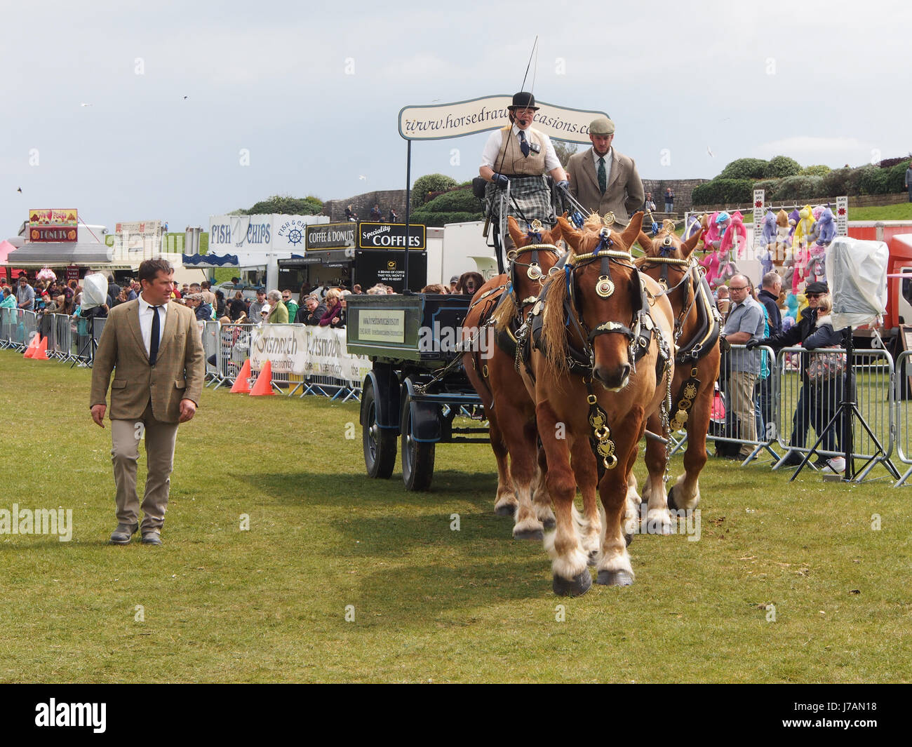 A cart drawn by four shire horses on display in an arena at a country show - Stock Image