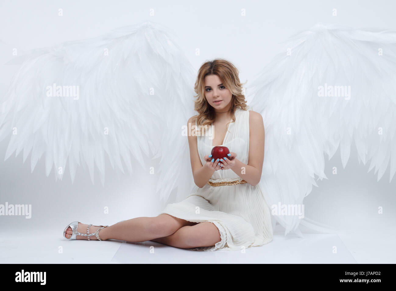 beautiful young model with big angel wings sitting in the studio - Stock Image