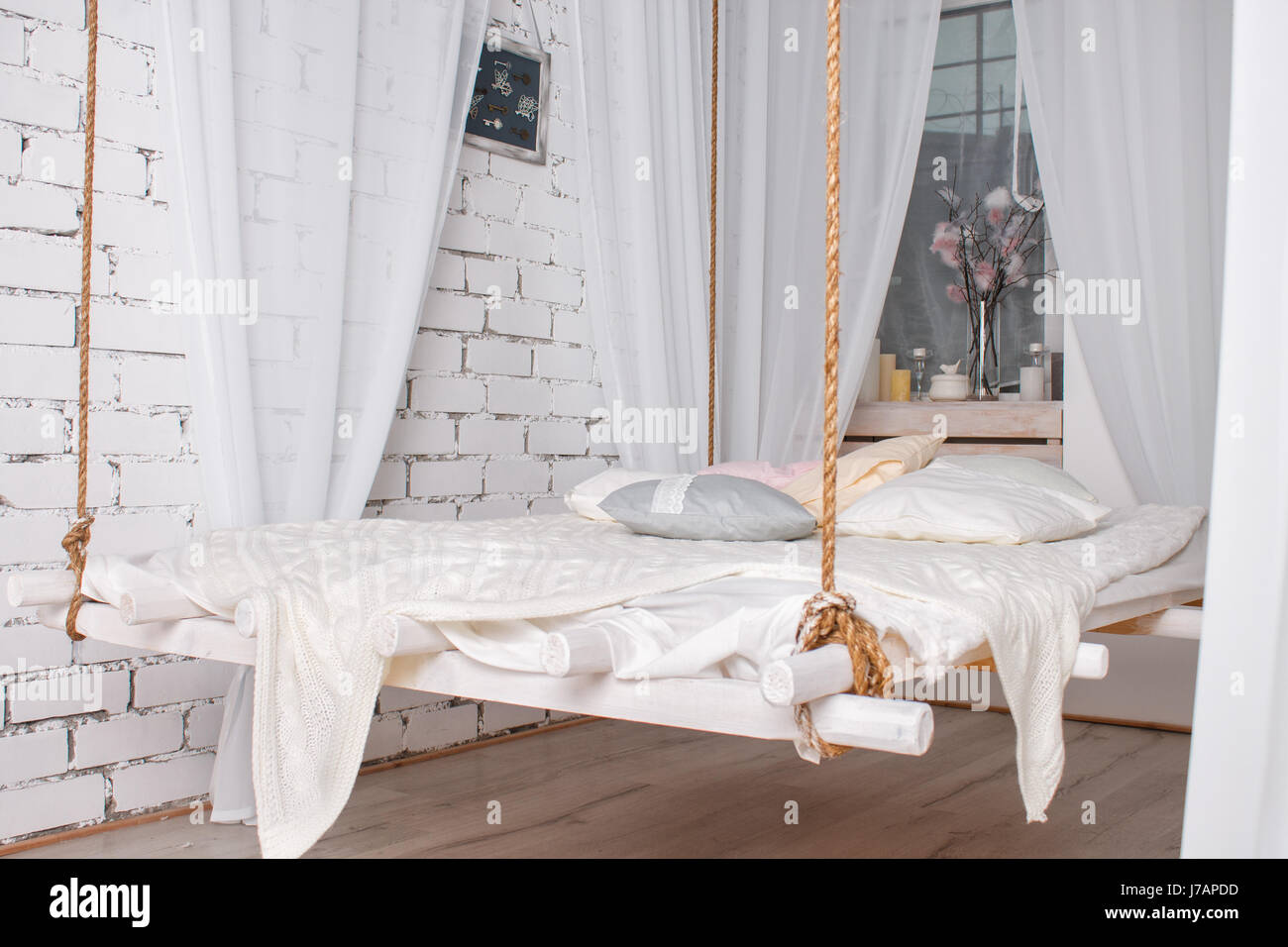 white loft interior with hanging bed suspended from the ceiling J7APDD