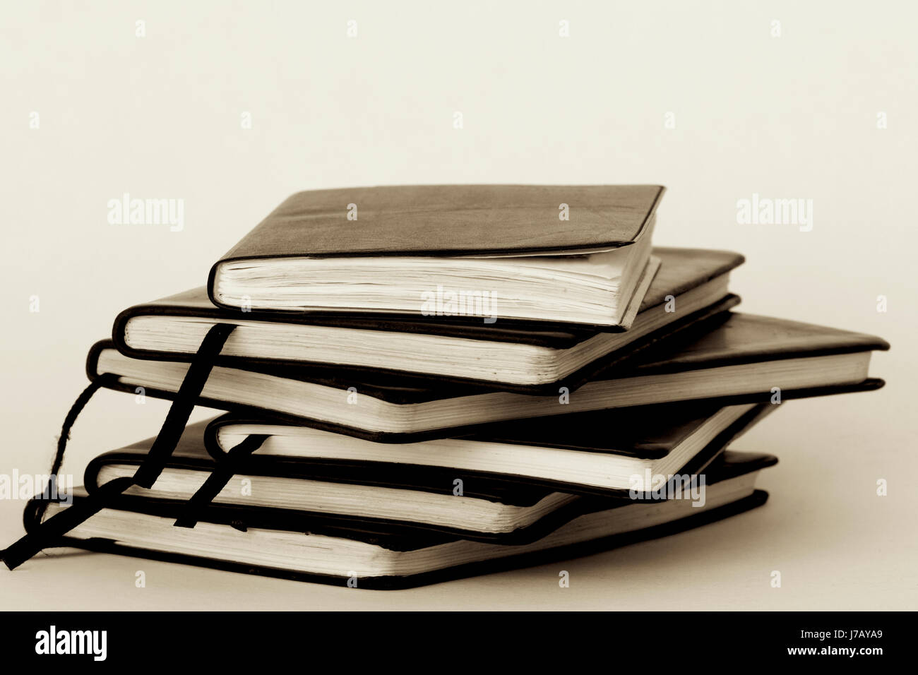 Stack of old leather covered diaries: black and white photo. - Stock Image