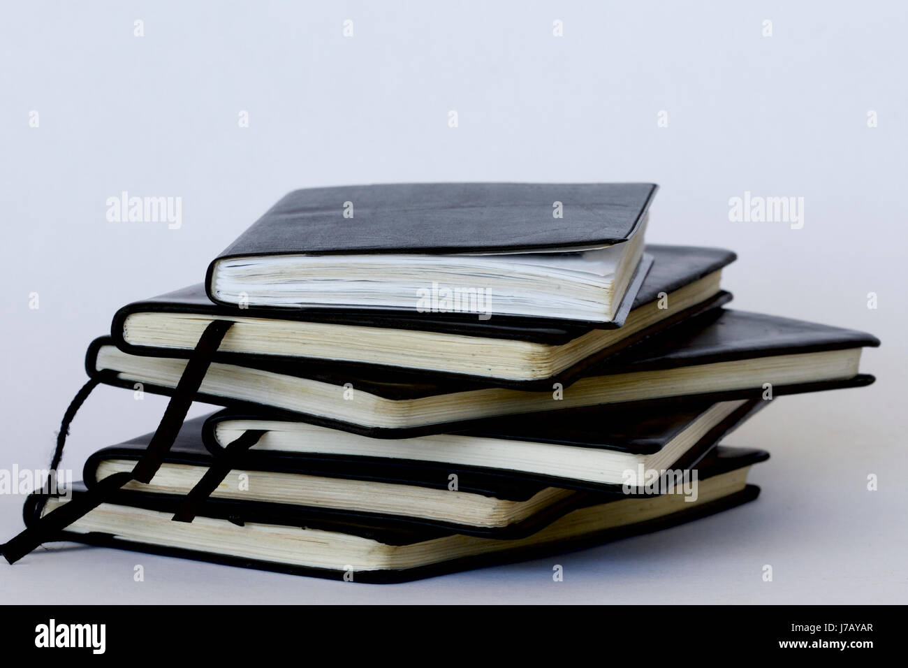 Stack of old leather covered diaries. - Stock Image