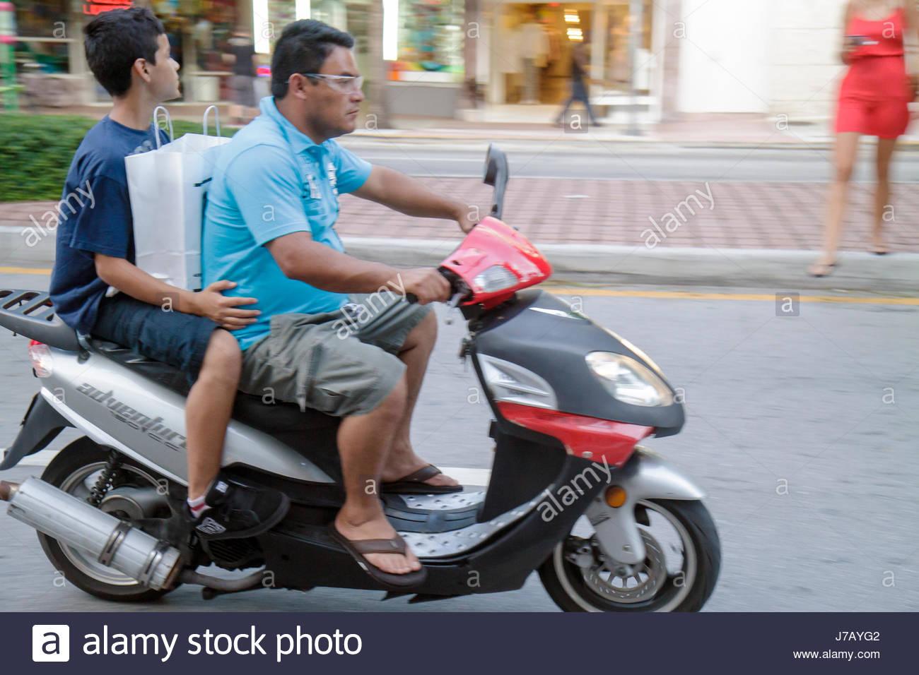 Miami Beach Florida Washington Avenue Hispanic man father boy son passenger moving motor scooter speed motion no - Stock Image