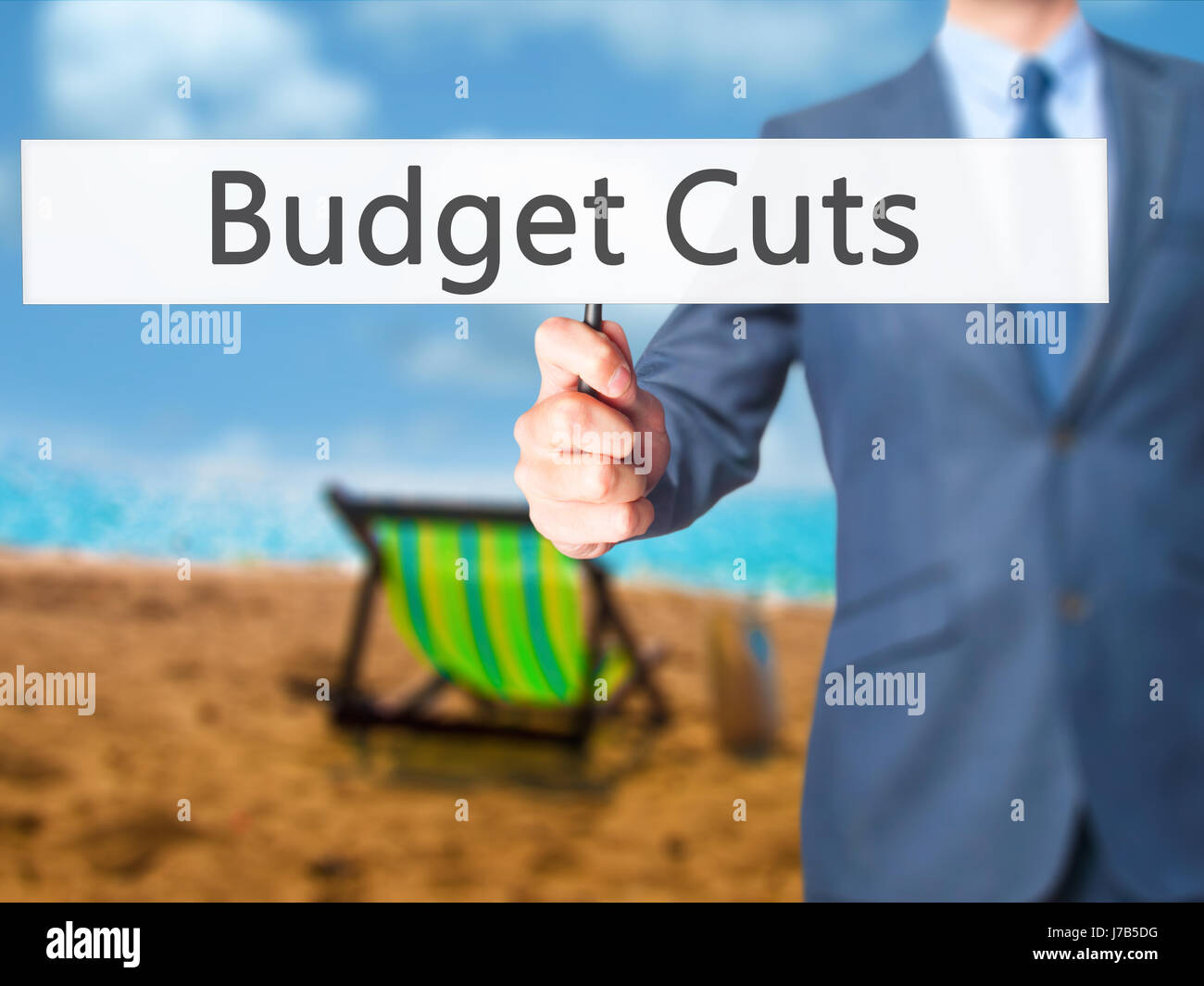 Budget Cuts - Businessman hand holding sign. Business, technology, internet concept. Stock Photo - Stock Image