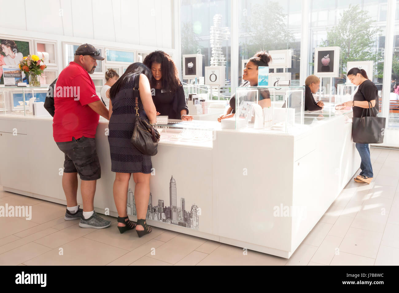 A saleswoman waiting on customers in a Pandora jewelry store in Midtown Manhattan, New York City, New York, USA. - Stock Image